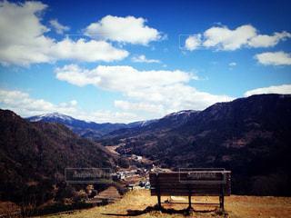山の上に座っている木製のベンチの写真・画像素材[2374542]