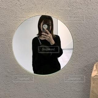 鏡で自分撮りをする人の写真・画像素材[2702956]