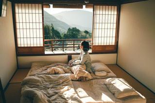 窓の隣のベッドに座っている人の写真・画像素材[3125867]