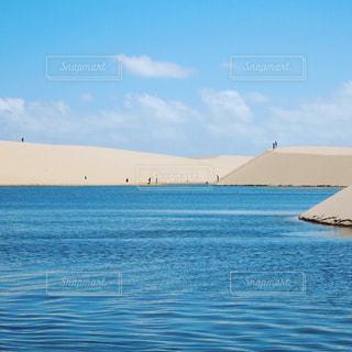 水の体の隣に座っている青と白のボートの写真・画像素材[2376221]