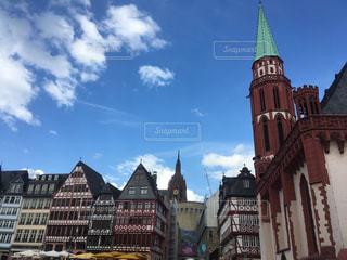 都市の上にそびえ立つ大きな時計塔の写真・画像素材[2376330]