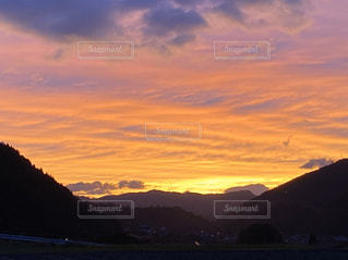 山を背景にした水域に沈む夕日の写真・画像素材[2959939]