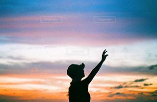 夕焼けに手を伸ばしたの写真・画像素材[2379655]