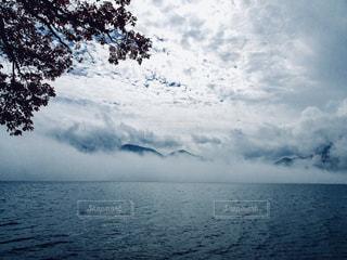 湖面を流れる霧とうろこ雲の写真・画像素材[2503105]