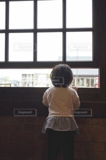 窓の前にたっている少女の写真・画像素材[4317446]