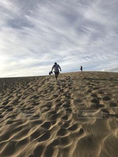 浜辺で空を飛んでいる男の写真・画像素材[2457010]