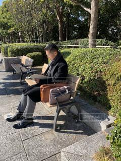 ベンチに座り仕事の資料を見ている男性の写真・画像素材[2884801]