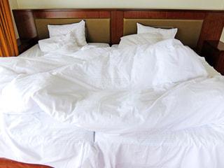 シーツと布団が乱れてるベッドの写真・画像素材[2497158]