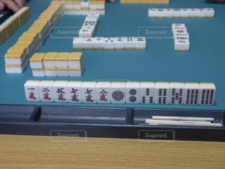 麻雀卓に並べられた手牌とリーチ棒の写真・画像素材[3081673]