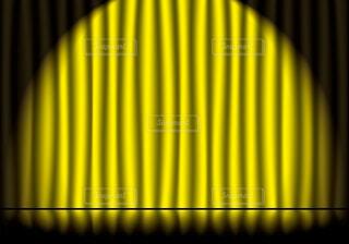 スポットライトが当たってる黄色のステージカーテンと反射している舞台の床の写真・画像素材[3990015]