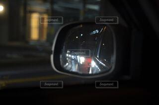 サイドミラーに映る渋滞中のヘッドライトが眩しい後続車の写真・画像素材[4074485]