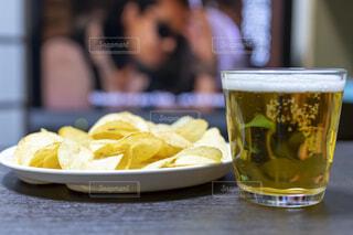 映画を見ながら食べるポテトチップスと晩酌用のビールの写真・画像素材[4662924]