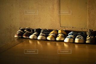 夕暮れの光が当たる玄関に並ぶ子供靴の写真・画像素材[4815881]