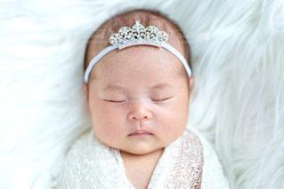 ティアラをつけて眠る赤ちゃんの写真・画像素材[2434823]