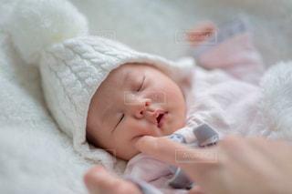 ほっぺたをプニプニ触られる赤ちゃんの写真・画像素材[2434831]