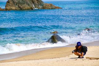 砂浜にしゃがんでいる女性の写真・画像素材[2436690]