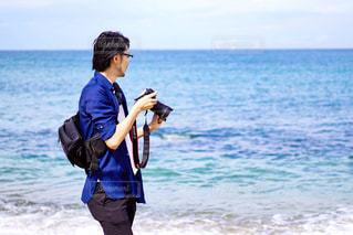 海辺でカメラを構える男性の写真・画像素材[2436696]