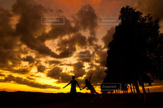 夕焼けと手を繋ぐカップルの写真・画像素材[2436811]