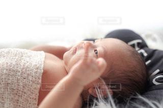 横になり宙を見つめる赤ちゃんの写真・画像素材[2438098]