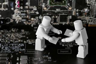 回路基板の上で名刺交換するビジネスマンのロボットの写真・画像素材[2410637]