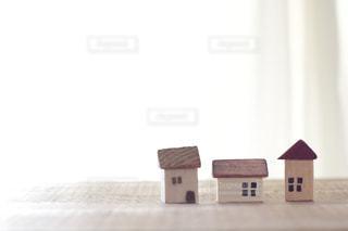 白いカーテンのそばに置いたマイホームのイメージの家のミニチュア模型の写真・画像素材[2410709]