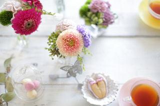 白い板の上に花🌼をコーディネートしたティータイムの写真・画像素材[2413157]