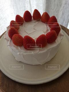 テーブルの上にショートケーキをトッピングした白い皿の写真・画像素材[2416346]