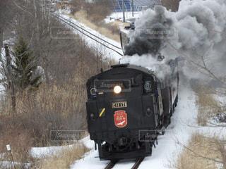煙突から煙が出る線路上の蒸気機関車の写真・画像素材[2997679]