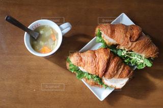 木製のテーブルの上に座っているサンドイッチの写真・画像素材[2432568]