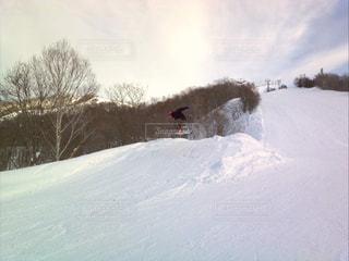 雪に覆われた斜面をスノーボードに乗っている男の写真・画像素材[2423810]