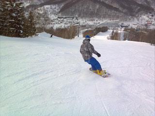 雪に覆われた斜面をスノーボードに乗っている男の写真・画像素材[2427329]