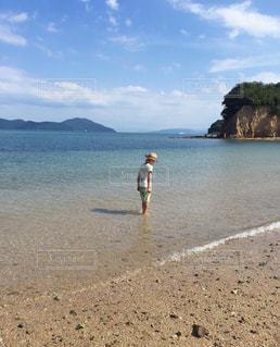 水域の近くの浜辺に立っている男の写真・画像素材[2432371]