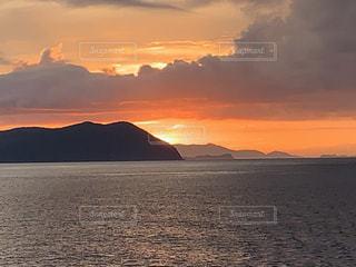 山を背景にした水域の夕日の写真・画像素材[2445012]