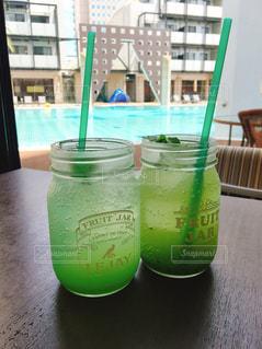 テーブルの上の緑色のガラスの写真・画像素材[2452729]