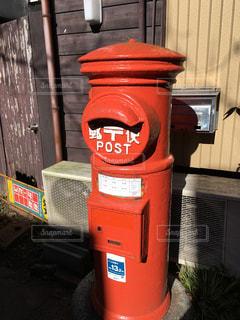 建物の側面に座っている赤い消火栓の写真・画像素材[2453124]