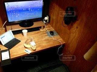 木製のテーブルの上に座っているデスクトップコンピュータの写真・画像素材[2457755]
