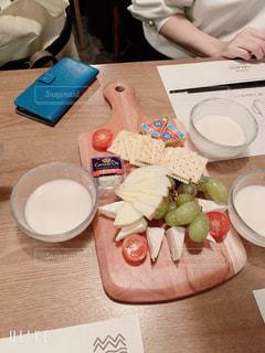 食べ物の皿を持ってテーブルに座っている人の写真・画像素材[2942220]