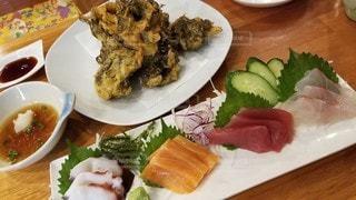食べ物の皿をテーブルの上に置くの写真・画像素材[3225767]