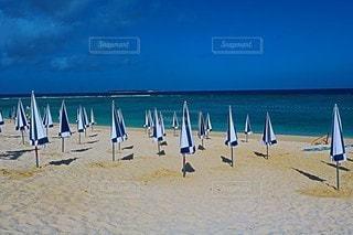 砂浜の上に座っている芝生の椅子のグループの写真・画像素材[3225777]