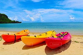 水の体の隣のビーチの上に座っているボートの写真・画像素材[3508190]