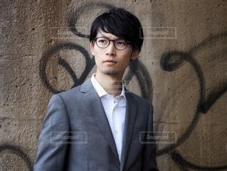 壁の前に立つビジネスマンの写真・画像素材[2509126]