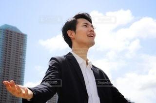 空を見上げ両手を広げる男性の写真・画像素材[2933624]
