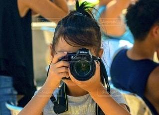 一眼レフカメラを構えて撮影する小学生の女の子の写真・画像素材[2513524]