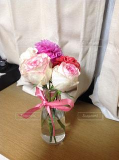 テーブルの上にピンクの花でいっぱいの花瓶の写真・画像素材[2500583]