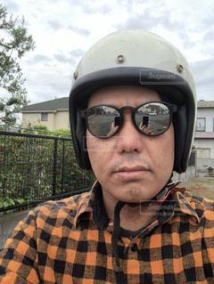 カメラのために帽子とサングラスをかぶった男の写真・画像素材[2212101]