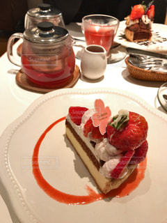 テーブルの上の桜のフレーバーティーと苺のタルトの写真・画像素材[1032403]