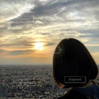 長い髪と背景に夕焼けを持つ人の写真・画像素材[2512174]