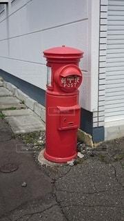 建物の側面に座っている赤いポストの写真・画像素材[2742547]