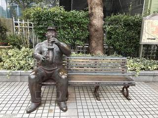 公園のベンチに座っている人の写真・画像素材[2514960]