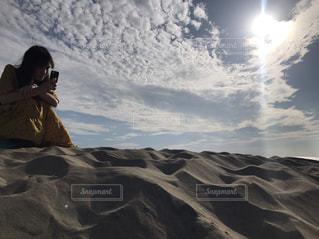 雪に覆われた砂の上に座っている人の写真・画像素材[2534340]